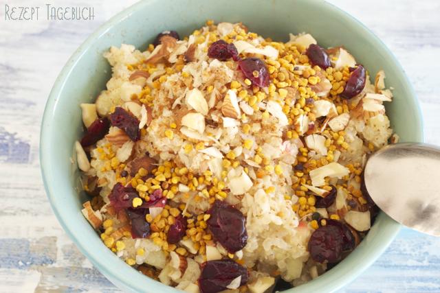 Quinoa Porridge mit roten Beeren Nüsen und Blütenpollen glutenfreies Frühstück